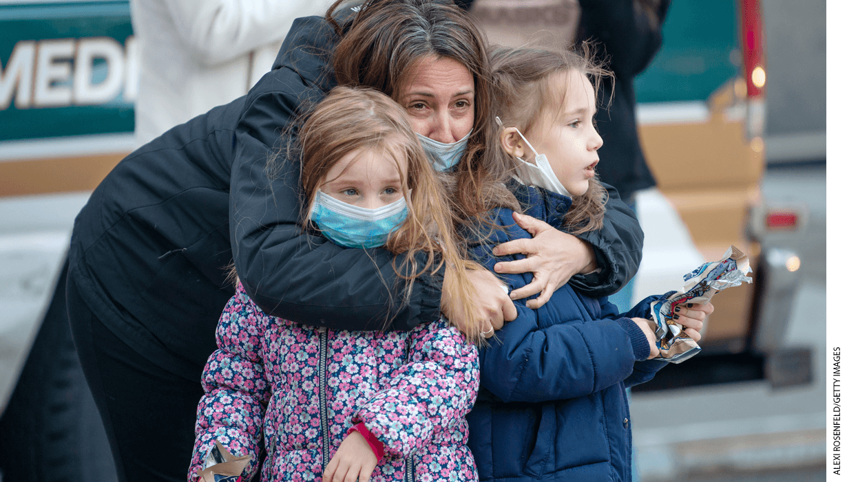 "A mother wearing a mask holds her two children outside of NYU Langone Health hospital during the nightly ""Clap Because We Care"" cheer for medical staff and essential workers."