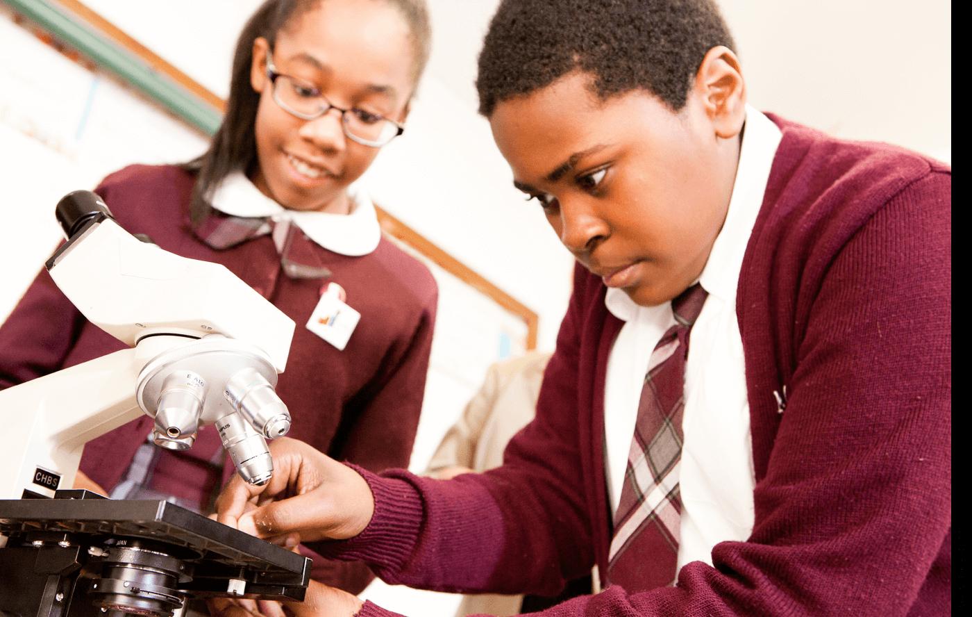 Students at Mt. Carmel-Holy Rosary School Catholic Elementary School in New York, N.Y., using a microscope