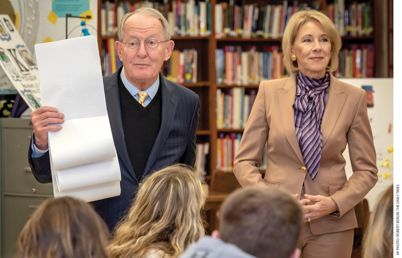 "Alexander, next to Secretary DeVos, holds up the Free Application for Federal Student Aid as students at the Sevier County High School in Tennessee watch. ""There are still too many questions on this form,"" Alexander says."