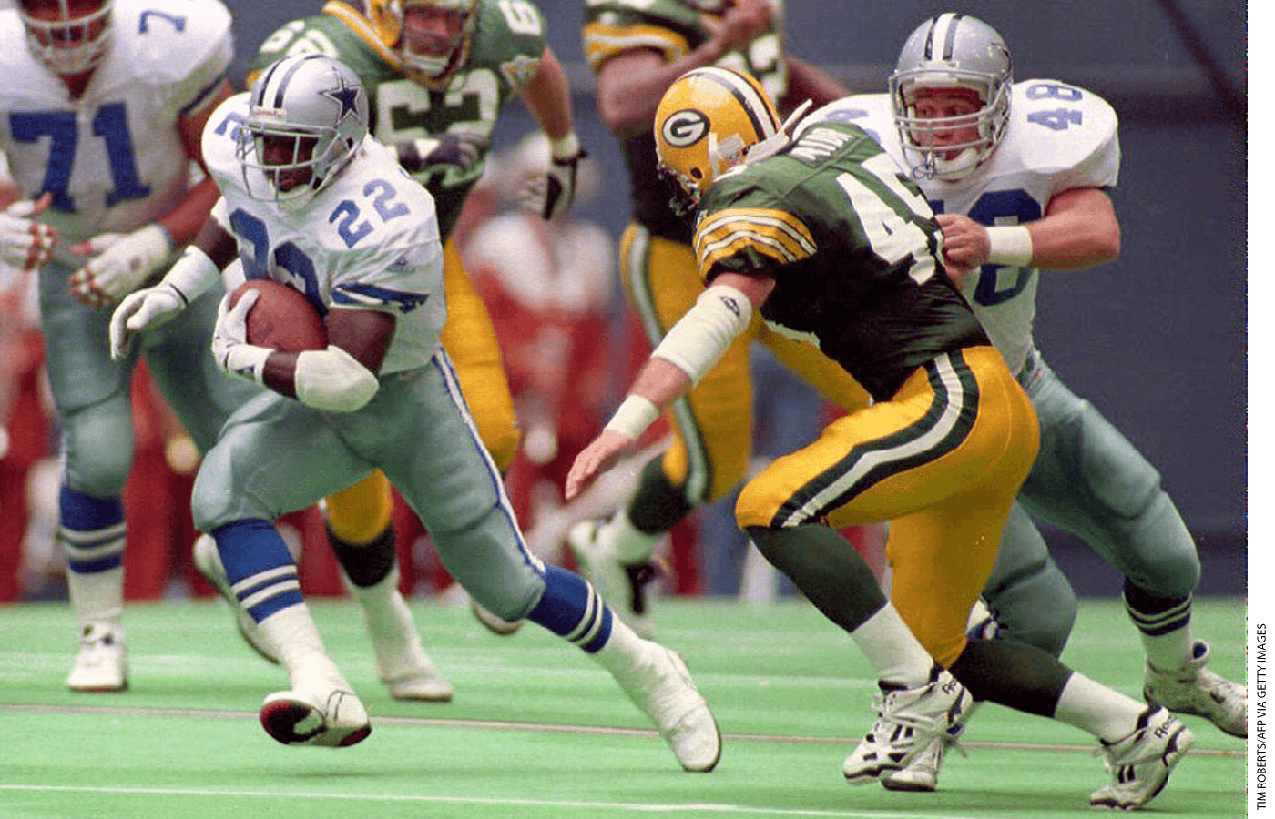 Dallas Cowboys running back Emmitt Smith (22) cuts around teammate Daryl Johnston (48) as Johnston makes a block on Green Bay Packers safety Mike Prior (45) during second quarter action 03 October 1993.