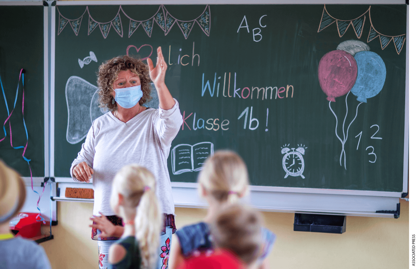 """Teacher Ditte M'ller welcomes the pupils of class 1b in front of the blackboard in the classroom of the primary school """"Werner Lindemann"""" on the first day of school in Mecklenburg-Western Pomerania, Germany, Aug. 2, 2021."""