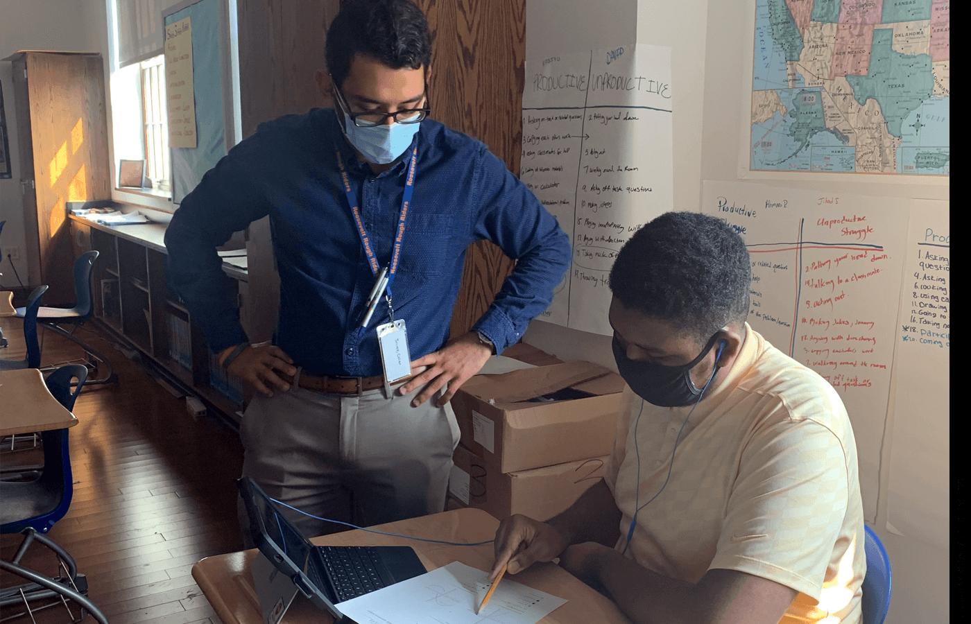 Roosevelt High math teacher Juarez Cesar helps a student with his work.